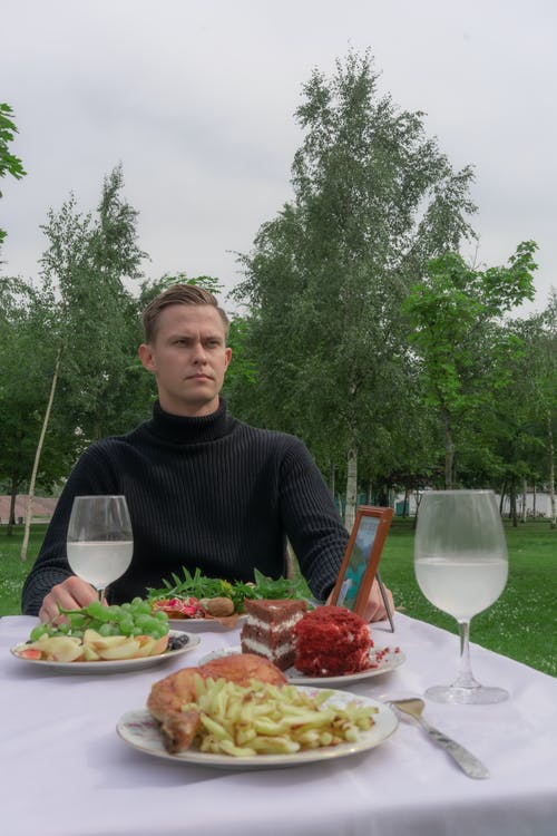 Serious man sitting at table with food