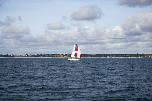 White Sail Boat on Sea Under Cloudy Sky