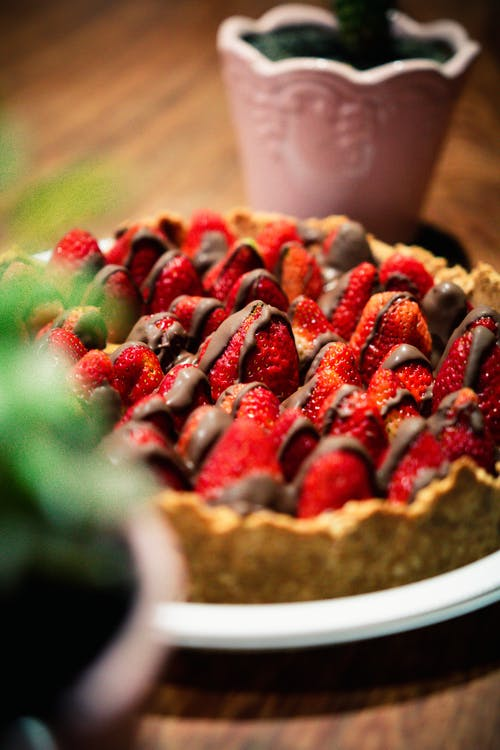 Delicious sweet cake with fresh strawberries with chocolate placed on wooden table