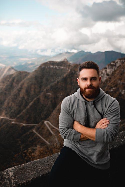 Bearded traveler sitting on stone fence against mountains