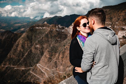 Happy couple enjoying hugging on viewpoint in highlands