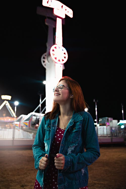 Cheerful young female in denim jacket and eyeglasses standing against shining glowing attraction in amusement park