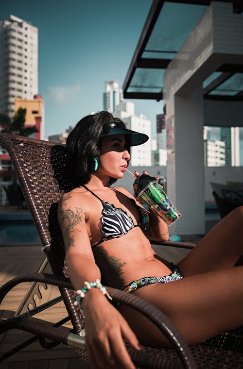 Side view of young female in swimwear listening to music in headphones while sunbathing with cup of fresh beverage