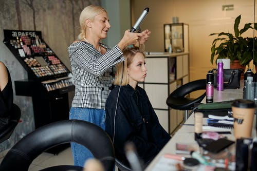 Side view of adult hairstylist straightening hair of client with iron in hairdressing salon