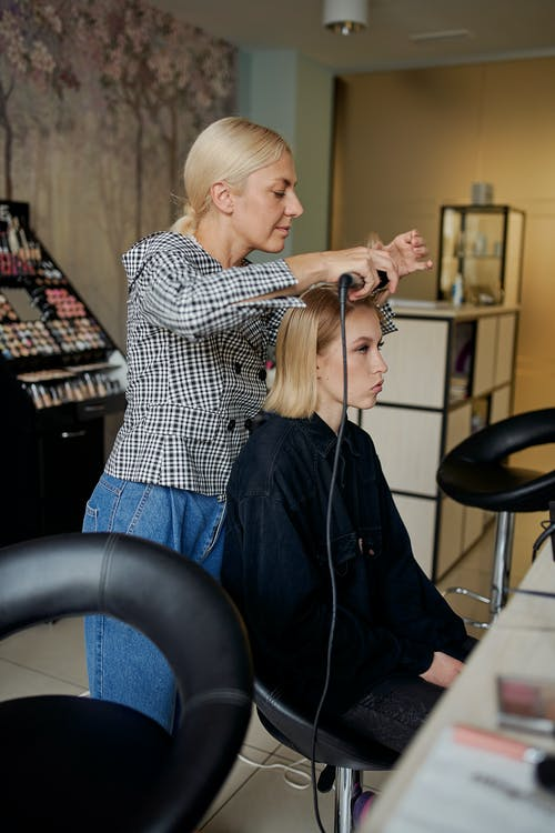 Hairstylist straightening hair of woman with iron