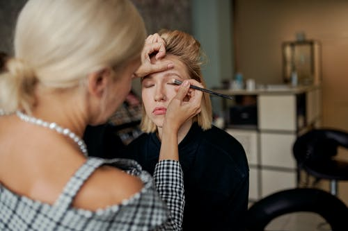 Unrecognizable visagiste applying eye shadow on face of woman