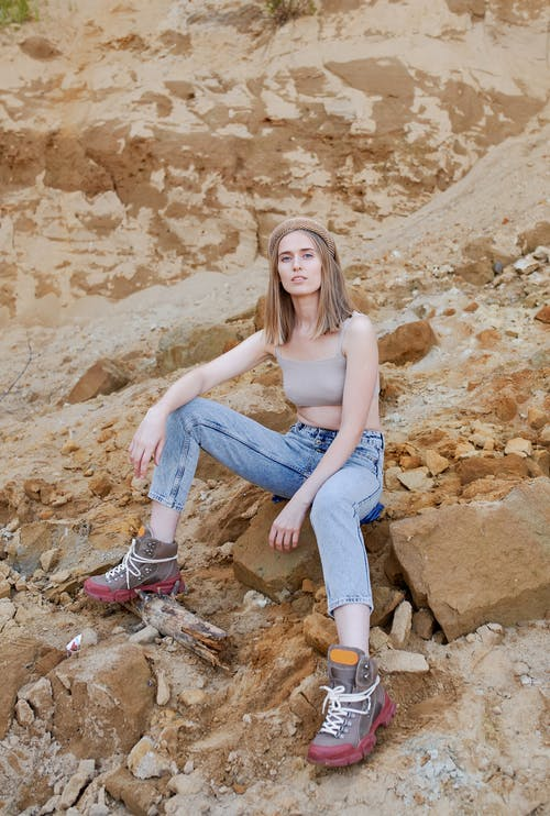 Trendy woman resting on rough rocks in summer