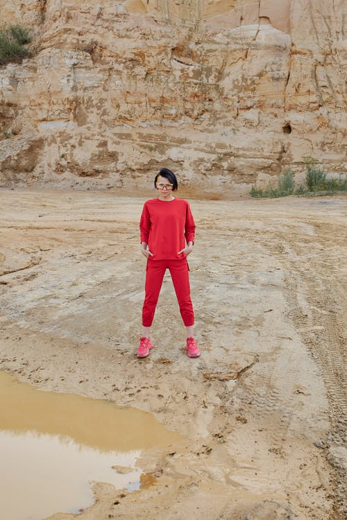 Young cool woman in trendy outfit standing with hands in pockets behind dry mountain and looking at camera