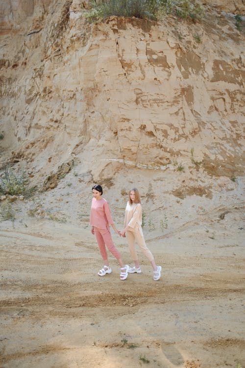 Unrecognizable trendy girlfriends holding hands in desert near mountain