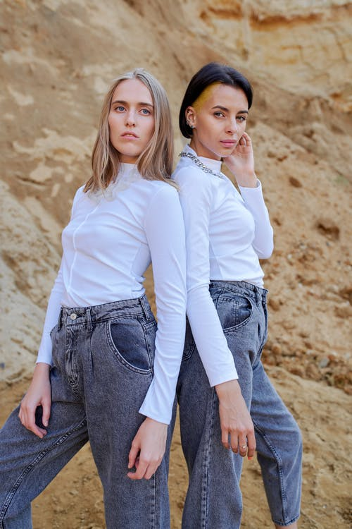 Young attentive female models in stylish clothes standing close on rough mount in summer