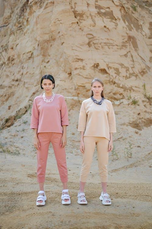 Women in stylish outfit near high mount in desert