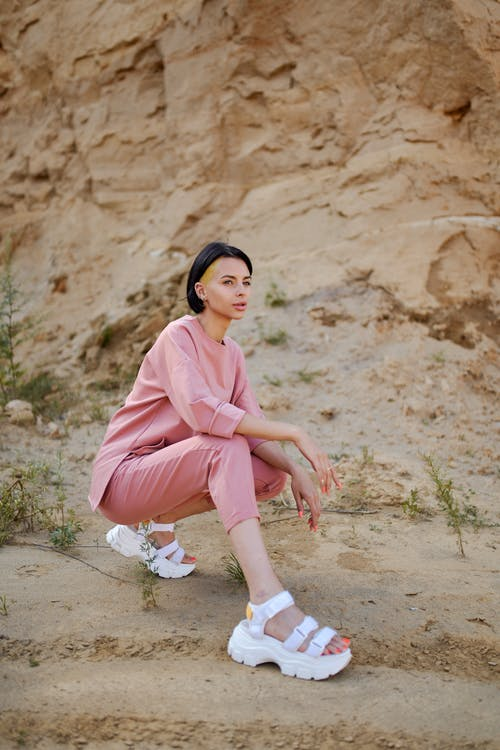 Stylish woman in modern sandals squatting in mountains