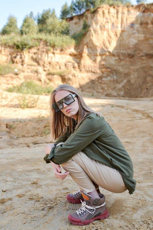 Stylish woman in modern sunglasses squatting near mount