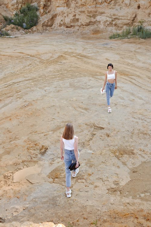 From above of anonymous women in similar trendy apparel strolling on sandy land near rock