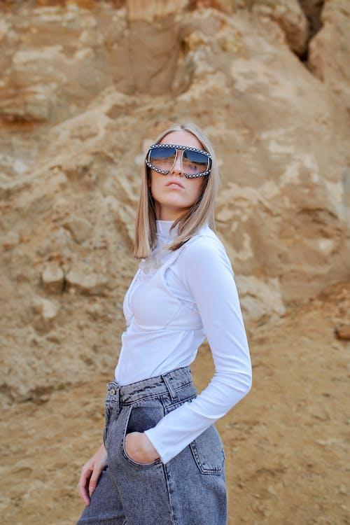 Trendy model in modern sunglasses near rock