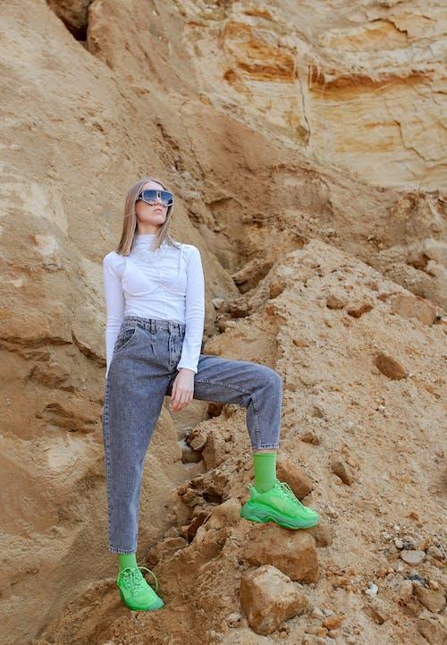 綠色運動鞋的時髦婦女在山