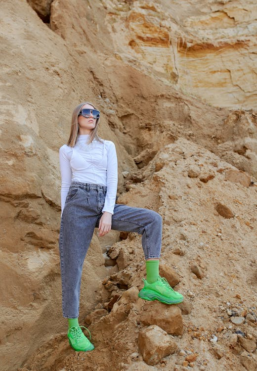 Young stylish female in bright apparel and contemporary sunglasses standing on dry rock in daylight