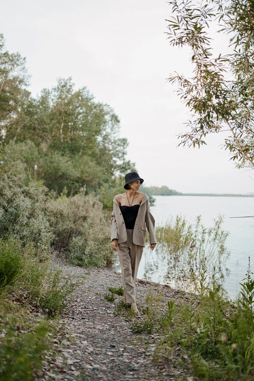 Stylish dreamy woman enjoying river while strolling on coast
