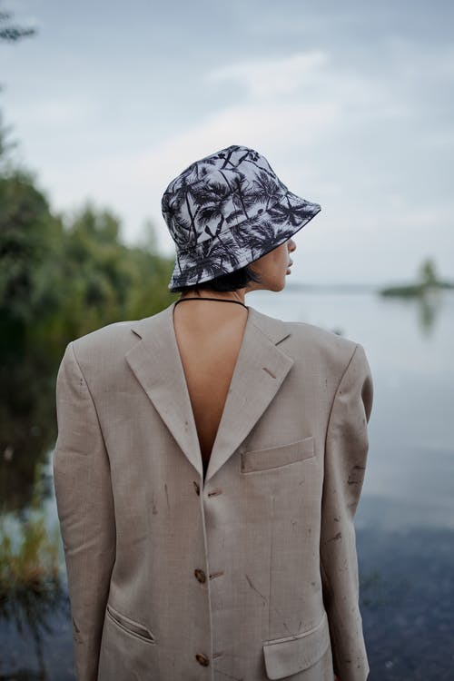 Back view of anonymous lady in ornamental panama hat and classic wear admiring river  in countryside