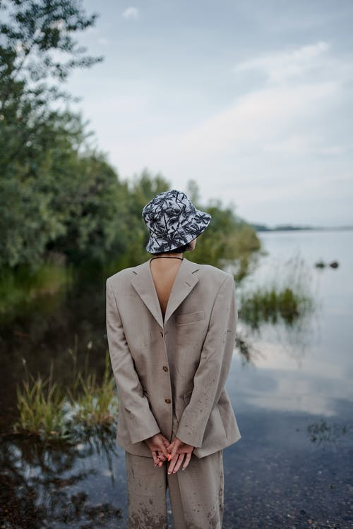 Back view of anonymous female in jacket worn backwards with hands behind back contemplating river in countryside