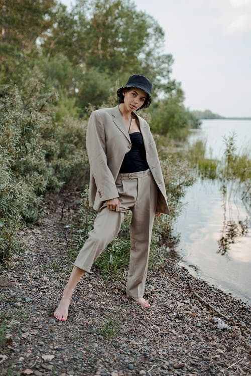 Stylish barefoot woman in suit on shore near river
