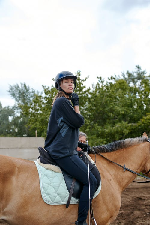 Confident horsewoman riding horse in countryside
