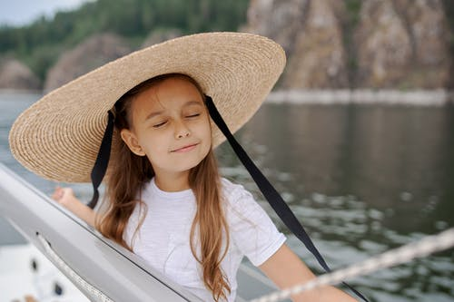 Cheerful child in straw hat with closed eyes enjoying summer day while standing on boat in sea