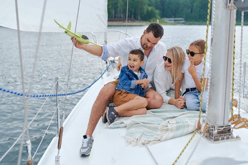 Full body of family in summer clothes having fun together on yacht in summer day