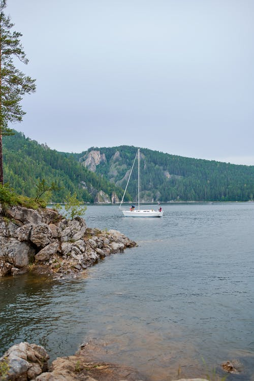 Picturesque view of calm water with boat near rocky shore against mountains with forest