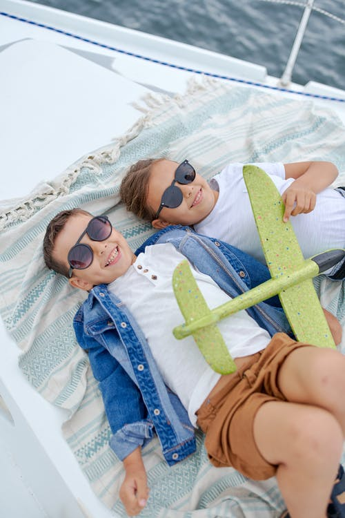 High angle of smiling boy and girl in sunglasses lying on yacht with toy plane and looking at camera