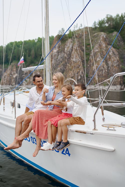 Full body of happy parents and children spending time together on sailboat in sea
