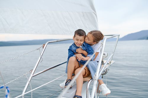 Little girl kissing brother on sailboat