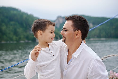 Side view of smiling father hugging little boy in summer shirt while spending time on boat in lake and looking at each other