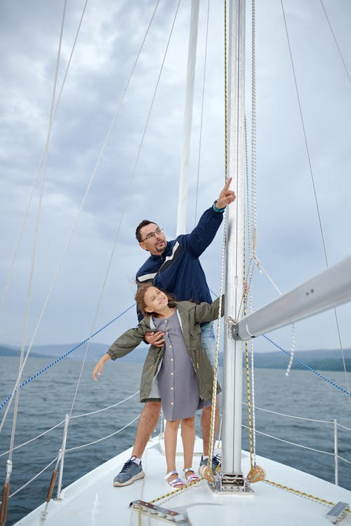 Man with daughter on sailboat in sea