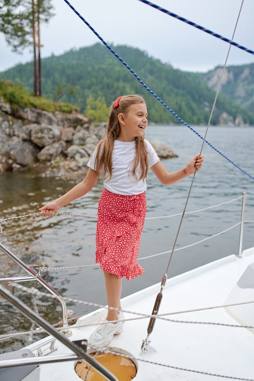 Full body of happy child in summer clothes standing on boat and laughing while spending time in nature