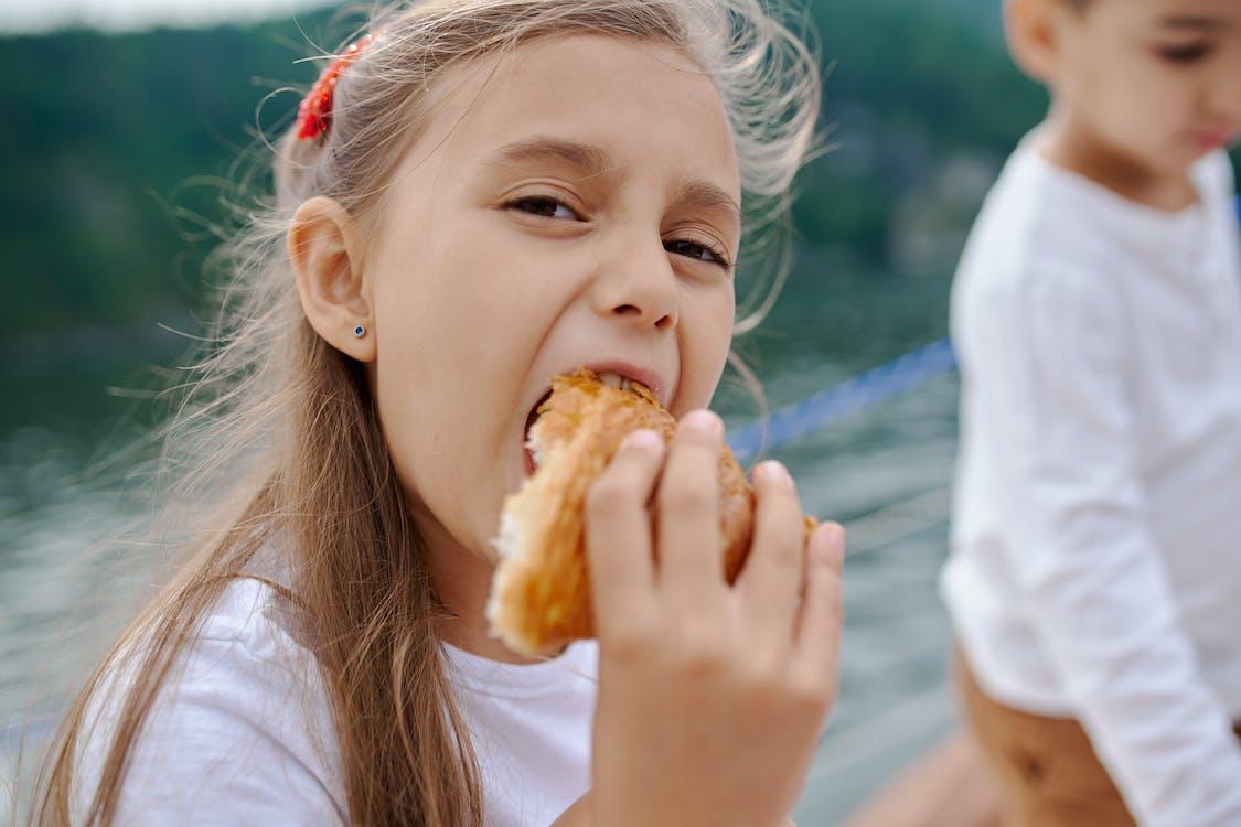 Happy little girl eating tasty croissant