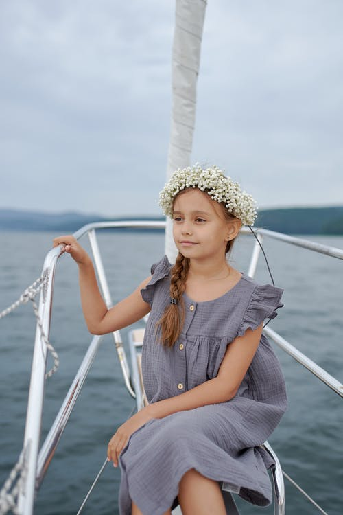 Stylish little girl resting on yacht