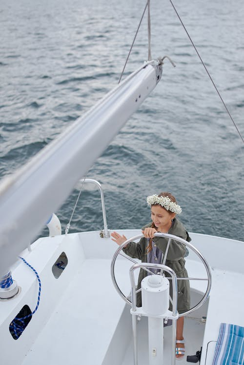 High angle of child in flower wreath and summer clothes standing near helm while floating on yacht