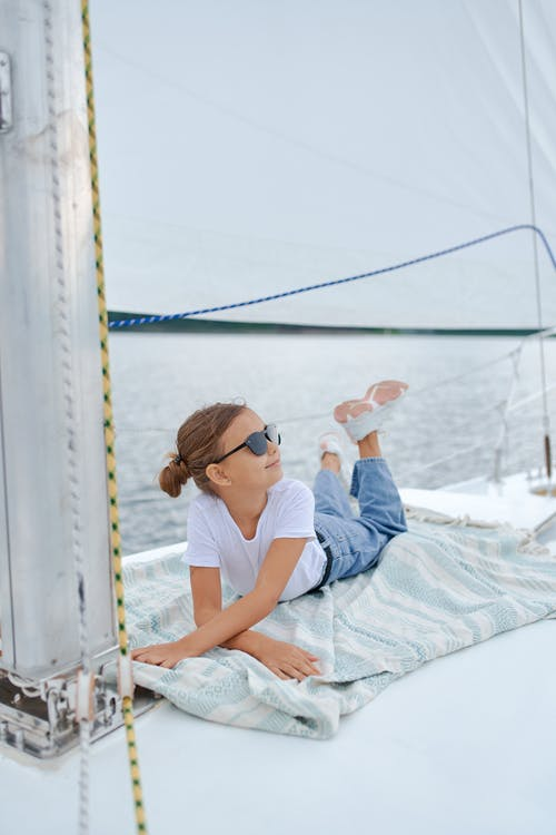 Little girl resting on sailboat in sea
