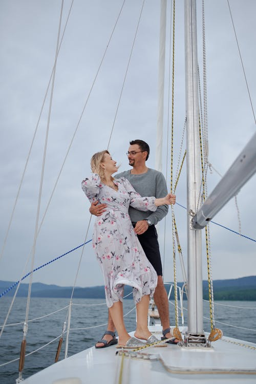 Full body of loving couple in summer clothes caressing on yacht while looking at each other