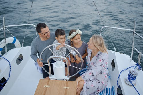 Happy family on yacht sailing on sea during trip
