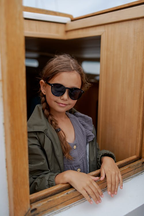 Smiling girl in sunglasses on yacht during trip