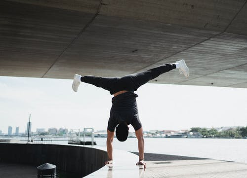 Faceless sportsman doing handstand and split in air