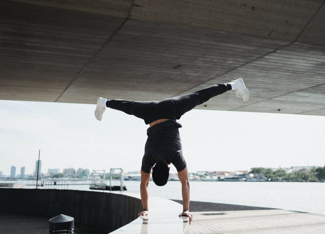 Back view full body strong sportsman performing handstand and split in air while working out on sunny city embankment