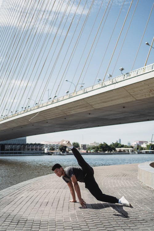 Sporty Asian man performing breakdance on city riverside