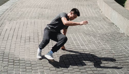 Energetic Asian man dancing street dance on sidewalk