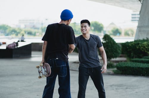 Smiling Asian men in street style clothes shaking hands and greeting each other while standing on sunny street