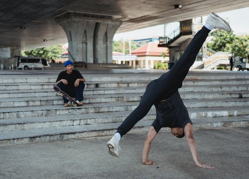 Sporty male dancer doing handstand dance movement