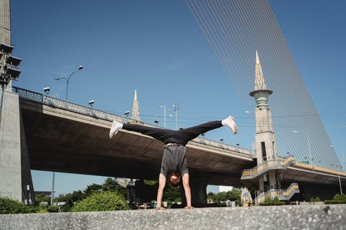 Energetic sportsman performing handstand and split in air