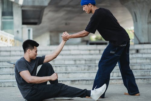 Asian man helping friend to get up from ground